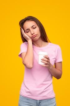 Slaperige vrouw met kop energieke koffie