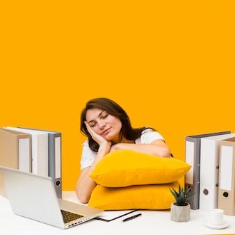 Slaperige vrouw met kussens op haar bureau