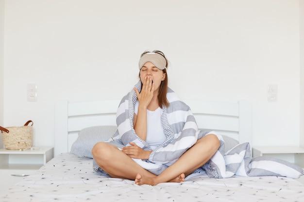 Slaperige vrouw met slaapmasker en gewikkeld in deken poseren binnen in lichte slaapkamer zittend op bed met gekruiste benen, mond bedekken met palm terwijl geeuwen.
