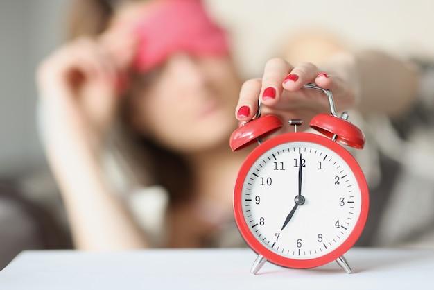 Slaperige vrouw reikt om zeven uur 's ochtends naar een rode wekker, slapeloosheid en wordt 's ochtends wakker