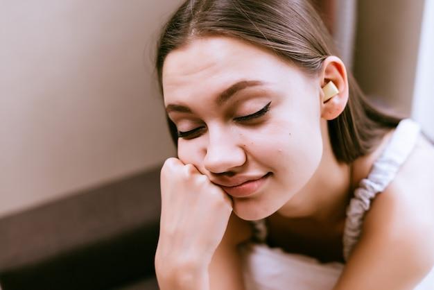 Slaperige vrouw zit op het bed met gesloten ogen op het bed