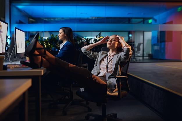 Slaperige vrouwen werken op computers in het nachtkantoor. slaperige vrouwelijke zakenvrouwen, donker zakencentruminterieur, moderne werkplek