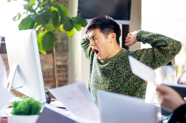 Slaperige zakenman geeuwt op kantoor
