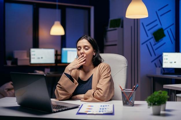 Slaperige zakenvrouw gaapt terwijl ze op een laptop werkt en een projectdeadline probeert af te maken. slimme vrouw zit op haar werkplek in de loop van de late nachturen en doet haar werk.