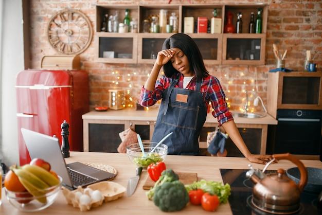 Slaperige zwarte die in schort gezond ontbijt op de keuken kookt. afrikaanse vrouwelijke persoon die groentesalade thuis voorbereidt