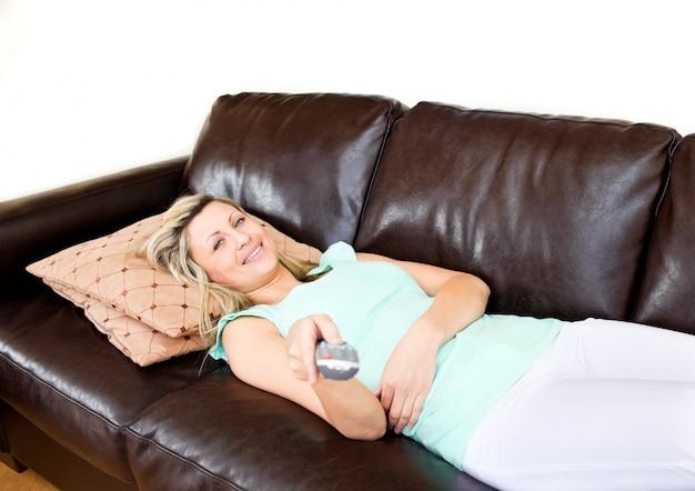 Slappe vrouw ligt op de bank en kijkt tv