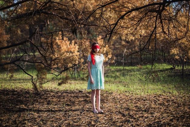 Slavernij. heel schattig jong meisje met een blinddoek rood lint. pop uiterlijk. vrouw met bruin haar in een turquoise jurk op de natuur. lang haar. natuurlijk licht. model poseren op de aard. ontvoering