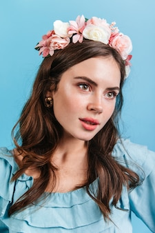 Slavisch meisje in zachte outfit kijkt in de verte. portret van een jonge vrouw met roze bloemen in golvend haar.