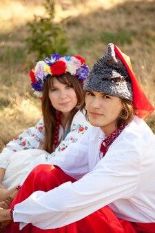 Slavische meisje met krans en jonge kozakken in de natuur.