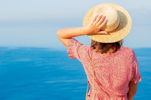 Slavische vrouw in een hoed bij de zee aan de rand van een klif.