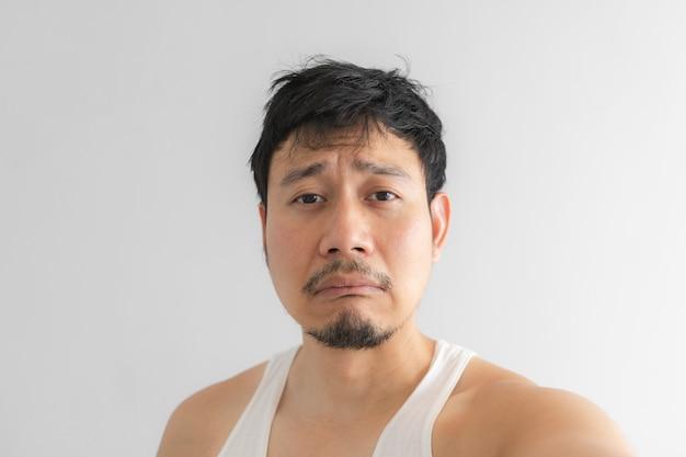 Slecht en gedeprimeerd gezicht van de mens op grijze achtergrond. concept van het wanhopige leven.