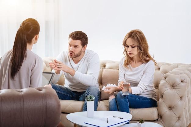 Slecht humeur. mooie ongelukkige jonge vrouw die een glas water en een tissue houdt en naar beneden kijkt terwijl ze naar haar echtgenoot luistert