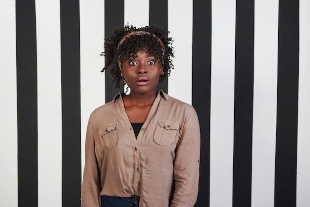 Slecht nieuws. mooi vrouwelijk portret op de zwarte en blauwe strepen typen achtergrond. afro-amerikaanse meisje maakt geschokt gezicht