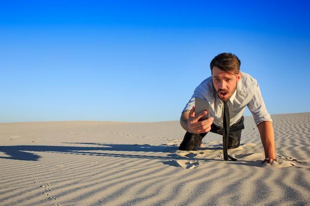 Slecht signaal. zakenman op zoek naar mobiele telefoon signaal in woestijn