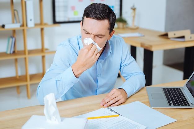 Slecht voelen. depressieve mannelijke persoon leunend op tafel en neus snuiten zittend op zijn werkplek