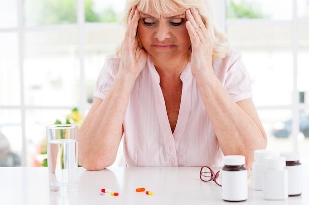 Slecht voelen. depressieve senior vrouw die het hoofd in handen houdt en naar de pillen kijkt die op tafel liggen