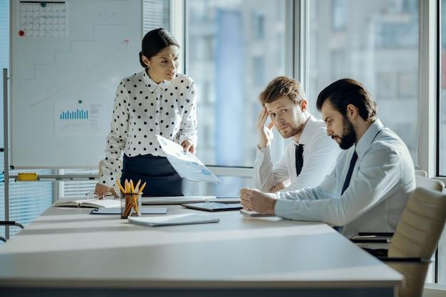 Slecht werk. boze vrouwelijke baas die een ontmoeting heeft met haar werknemers en hen berispt voor de slechte prestaties terwijl ze er beschaamd uitzien