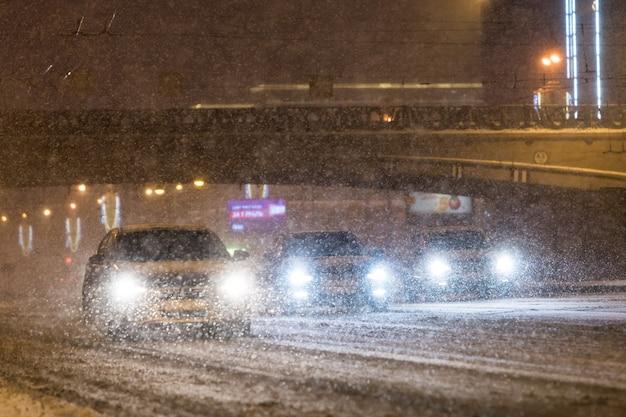 Slecht winterweer en slecht zicht. auto's rijden op de rijbaan tijdens een sneeuwstorm