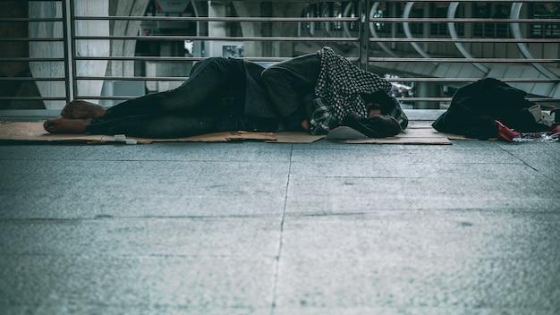 Slechte dakloze man of vluchteling die op de vloer van openbare wegmanier in de stad slapen
