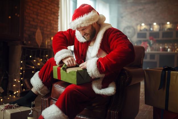 Slechte dronken kerstman opent geschenken onder de kerstboom