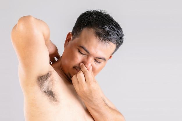 Slechte geur onderarmuitslag: man controleert en ruikt zijn oksel.