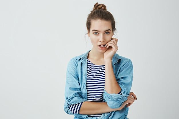 Slechte gewoonten brengen problemen met zich mee. studio shot van bezorgd of denken aantrekkelijk meisje met knot kapsel bijten vingernagels terwijl serieus op zoek, wordt gefocust terwijl het oplossen van iets