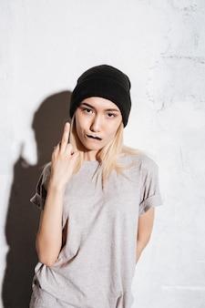 Slechte onbeleefde jonge vrouw in zwarte hoed die middelvinger toont