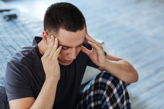 Slechte staat. arme donkerharige man zit en heeft vreselijke hoofdpijn