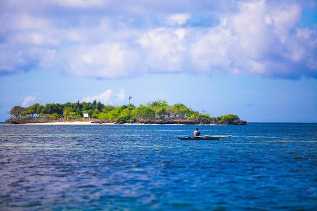 Slechte visser in boot bij duidelijke blauwe overzeese filippijnen