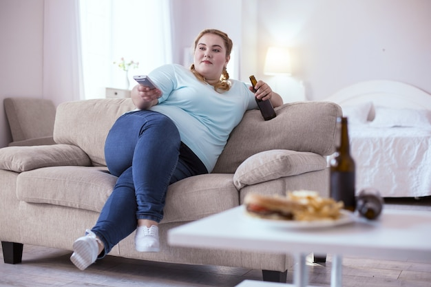 Slechte voeding. stout roodharige vrouw bier drinken tijdens het kijken naar televisie