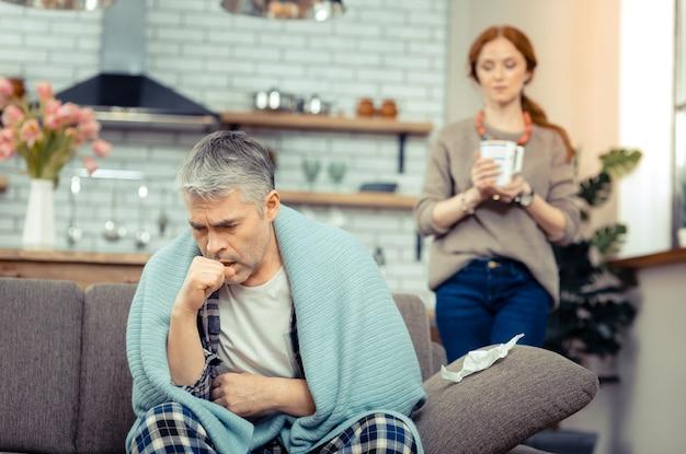 Slechte ziekte. trieste zieke man hoest terwijl hij lijdt aan bronchitis
