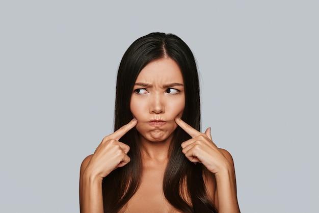 Slechtgehumeurd. ontevreden jonge aziatische vrouw die een gezicht trekt terwijl ze tegen een grijze achtergrond staat