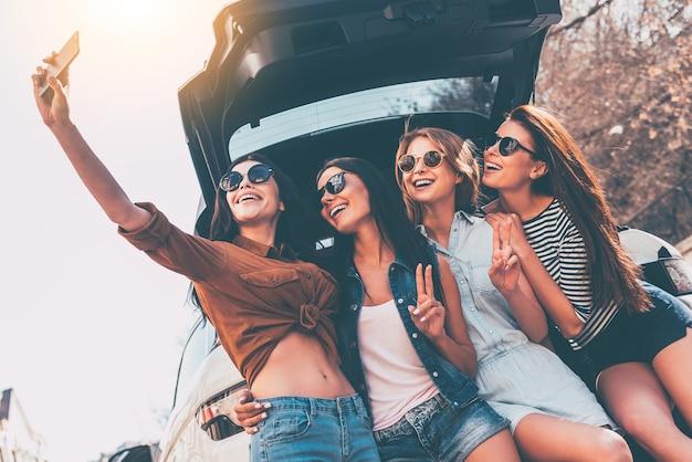 Slechts één selfie voor de roadtrip! vier mooie jonge vrolijke vrouwen die selfie maken met een glimlach
