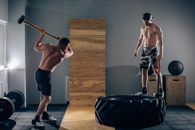 Sledgehammer tire hits mannen trainen in de sportschool met hamer en tractorband