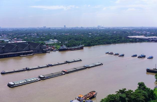 Sleepboten slepen zandbakken langs chao phraya-rivier