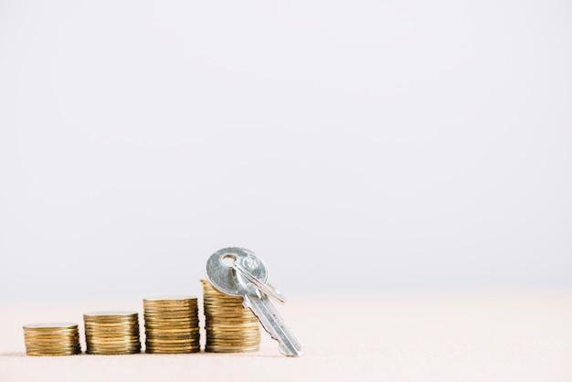 Sleutel in de buurt van stapels munten