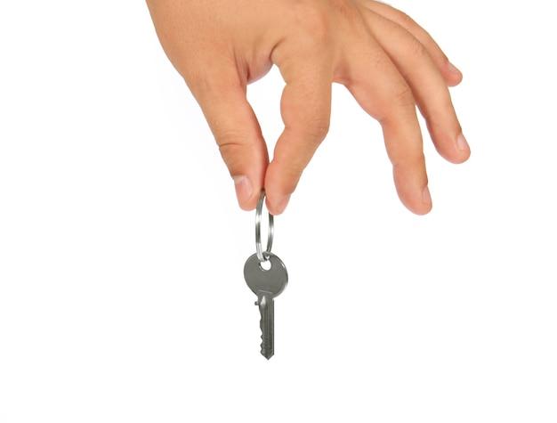Sleutel in de hand geïsoleerd op een witte achtergrond