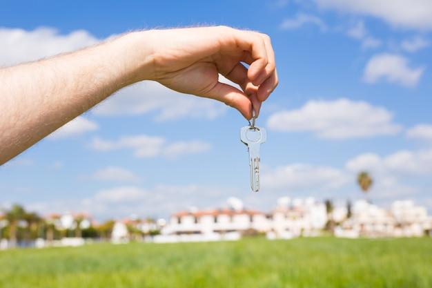 Sleutel in de hand voor nieuw huis en onroerend goed concept van housewarming huurder en nieuw huis