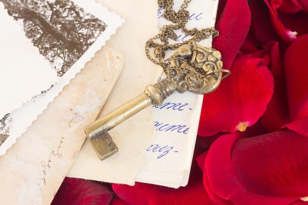Sleutel met oude papieren en karmozijnrode rozenblaadjes als symbool van liefde