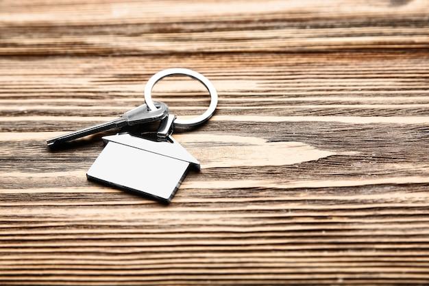 Sleutel met trinket in vorm van huis op houten. hypotheek concept