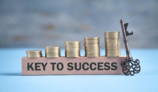 Sleutel tot succes met een sleutel en munten.