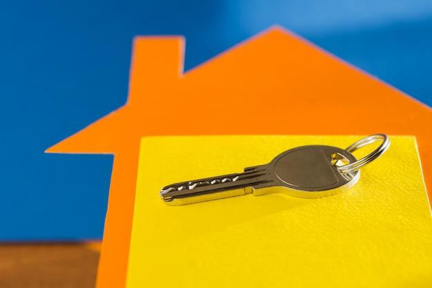 Sleutel voor onroerend goed op de achtergrond van een huis gemaakt van karton