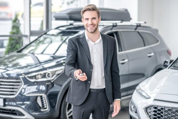 Sleutelhanger. glimlachende jonge volwassen man in pak met sleutelhanger in de hand staande in autodealer