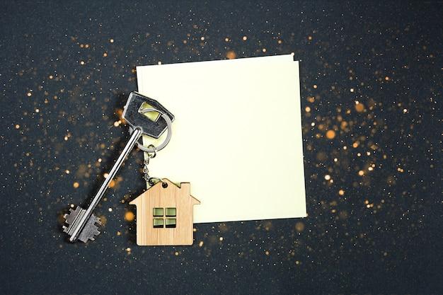 Sleutelhanger in de vorm van een houten huisje met sleutel op een zwarte achtergrond met een vierkant blad voor notities.