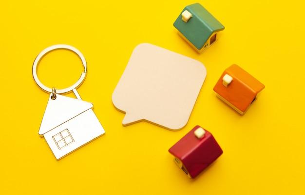 Sleutelhanger in de vorm van een huis en speelgoed huizen op een gele achtergrond