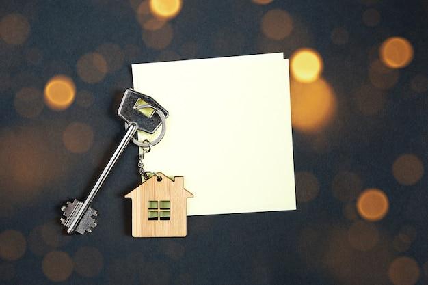 Sleutelhanger in de vorm van houten huis met sleutel op een zwarte achtergrond met kopie ruimte