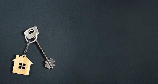 Sleutelhanger in de vorm van houten huis met sleutel op een zwarte achtergrond