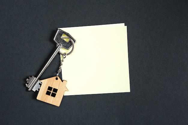Sleutelhanger in de vorm van huis met sleutel op een zwarte achtergrond met een vierkant blad voor notities.