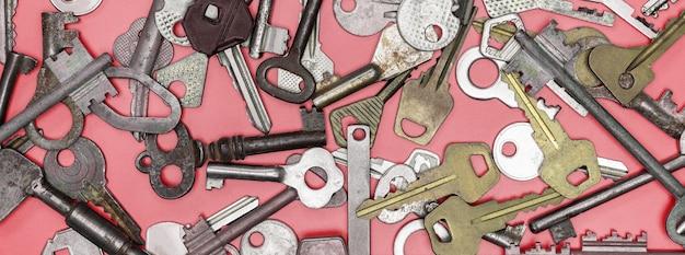Sleutels die op roze achtergrond worden geplaatst. deurslot sleutels en kluizen voor de beveiliging van eigendommen en huisbescherming. verschillende antieke en nieuwe soorten sleutels.