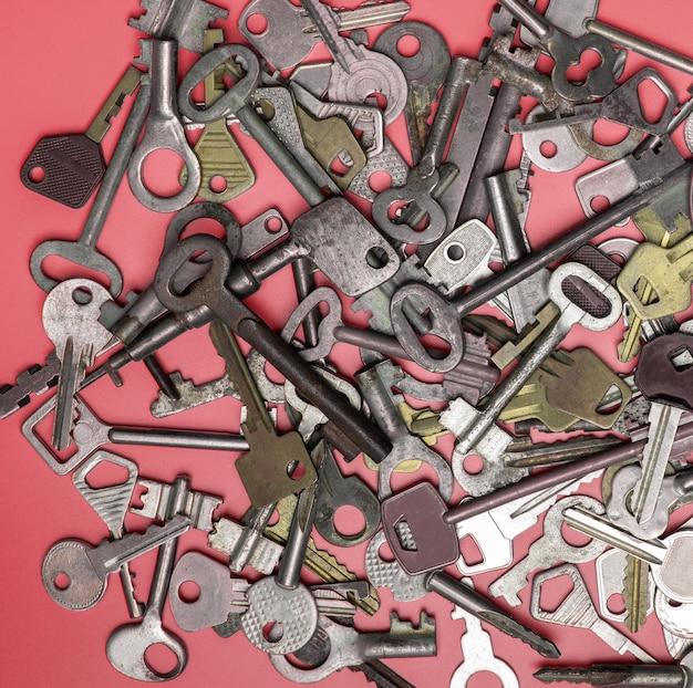 Sleutels die op roze achtergrond worden geplaatst. deurslot sleutels en kluizen voor de beveiliging van eigendommen en huisbescherming